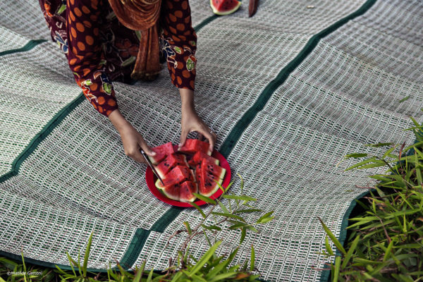 "Indonesia - Bangka Island - Rebo - A young mother serving watermelon to her family during a Friday supper. According to researches if lands are not properly reclamated the soild remains toxic and therefore vegetables and fruits which are grown will be radioactive. ""The impact of the destruction we are seeing now will last decades, if not centuriesî he predicts. ìSome species of fauna are already disappearing, as well as some high quality wood forest plants. If action is not taken now, something really bad will happen to this land."""